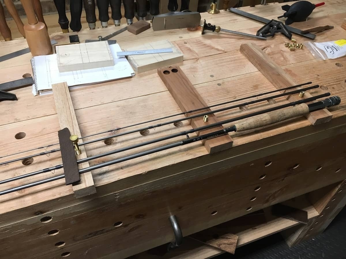 fly rod laid out on bench
